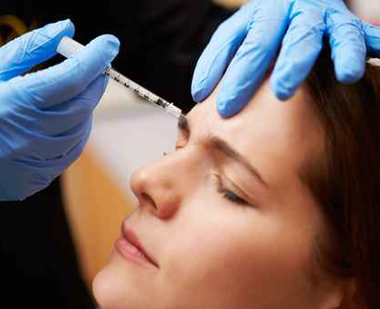Woman being injected with Botox in her eyebrow